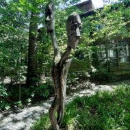 Holzfigur Wald vor Holzgebäude